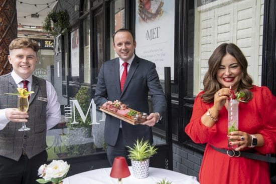 The Metropole managers showing prosecco cocktails on their outdoor terrace