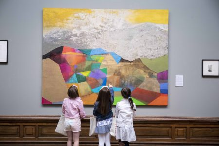 Three little girls examining a piece of artwork in the Crawford Art Gallery