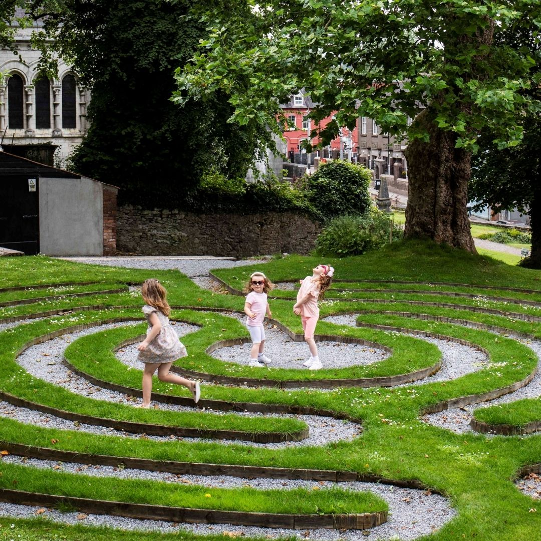 Three young girls playing in the labrynth at St Fin Barres Cathedral Cork City